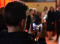 Junge hält ein Smartphone in der Hand und fotografiert