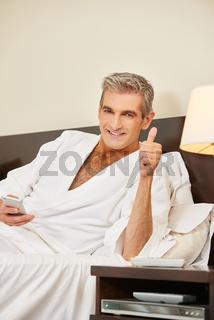 Mann  im Hotelzimmer hebt den Daumen hoch