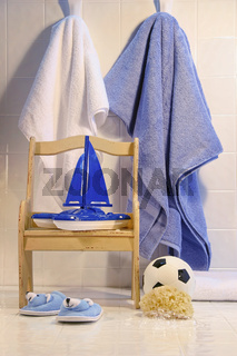 Toys with chair and towels on bathroom floor