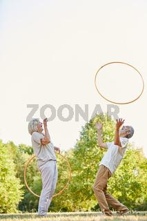 Paar Senioren trainiert lachend mit Reifen