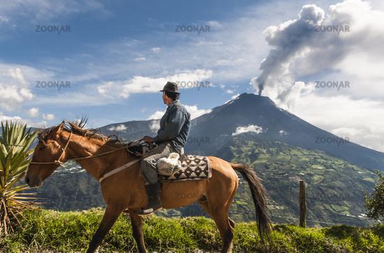 BANOS, ECUADOR - DECEMBER 10: Unrecognizable farmer on a horse looking at the  Tungurahua volcano eruption - december 10, 2010 in Banos, Cordillera Occidental of the Andes of central Ecuador, South America