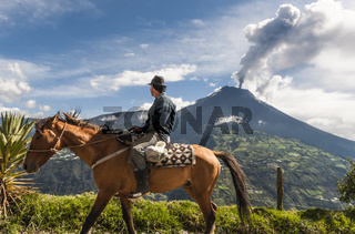 BANOS, ECUADOR - DECEMBER 10: Unrecognizable farmer on a horse looking at the  Tungurahua volcano eruption - december 10, 2010 in Banos, Cordillera Occidental of the Andes of central Ecuador, South America
