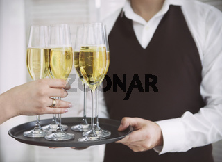Woman taking one glass of champagne from the tray