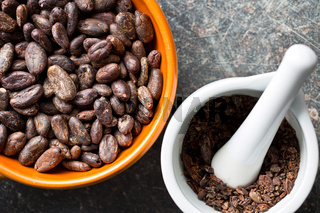 cocoa beans in bowl and mortar