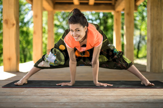 Girl makes wide-legged forward bend