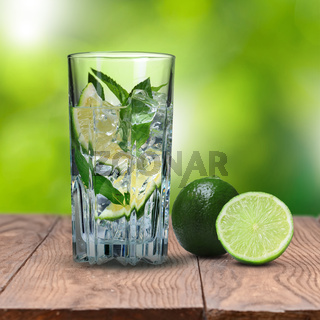 mohito cocktail on wooden table against green background
