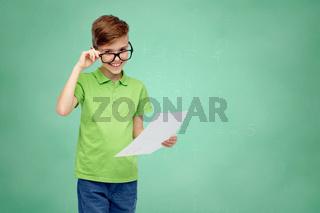happy boy in eyeglasses holding school test result