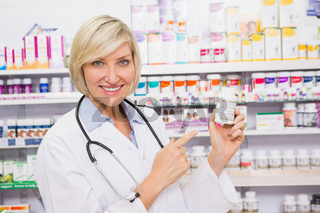 Smiling doctor pointing a drug bottle