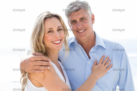 Happy couple standing by the sea and smiling at camera