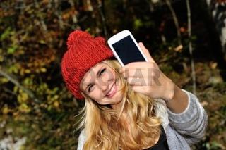 Junge Frau mit roter Mütze macht ein Selfie