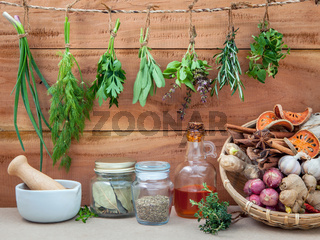 Assorted hanging herbs ,parsley ,oregano,sage,rosemary,sweet basil,dill,spring onion  and  set up with dry and fresh thyme ,bay leaves,sesame oil ,cinnamon ,star anise  for seasoning concept on rustic old wooden background.