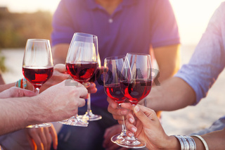 People holding glasses of red wine making a toast at the beach
