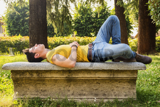 Attractive young man sleeping on stone bench outdoor