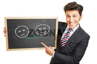 Mann zeigt Smileys glücklich und unglücklich