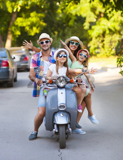 Happy young family riding a vintage scooter in the street wearing hats sunglasses