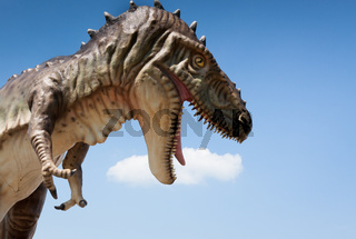 Tyranosaur T-rex dinosaur figurine over blue sky background
