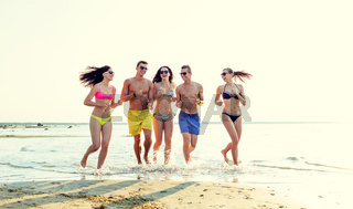 smiling friends in sunglasses running on beach