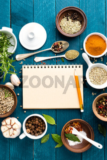 culinary background and recipe book with various spices on wooden table