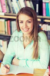 happy student girl writing to notebook in library