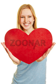 Frau hält rotes Herz als Symbol für Liebe