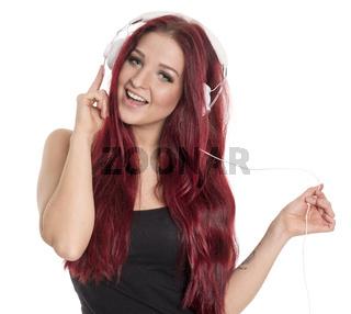 rothaarige frau mit kopfhörer lauscht der musik