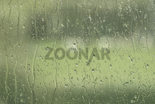 Window with rain drops in green color