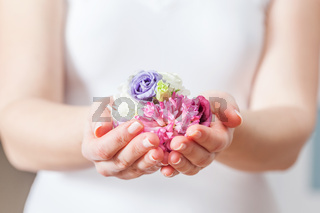 Fresh flowers in woman hand. Concept of beauty and spa, health care.