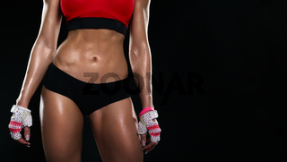 The body of young athletic girl on a dark background