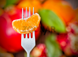 Tangerine slice on fork,  bright colored background