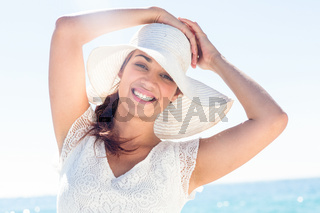 Pretty brunette wearing sunhat and looking at camera