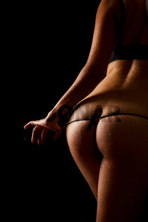 Woman pulling off her underwear over black background.