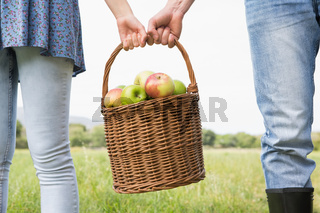 Couple holding basket full of apples