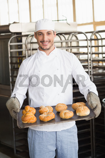 Baker showing tray of rolls