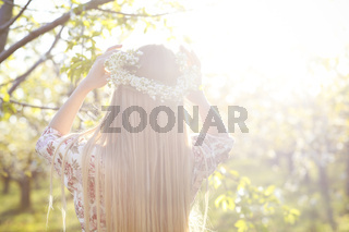 Beautiful romantic woman with long blond hair in a wreath