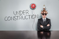 Under construction text with alert light and vintage businessman