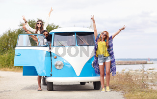 smiling young hippie friends over minivan car