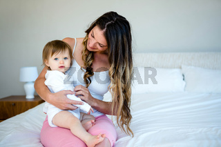 brunette woman holding a baby on a bed