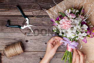 Making a bouquet from gillyflowers and alstroemeria on old wooden background with wooden heart and scissors with paper