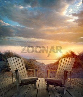 Wooden deck with chairs, sand dunes and ocean