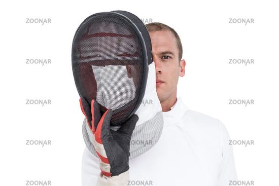 Swordsman holding fencing mask