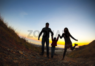 Silhouette of two happy adults and a child