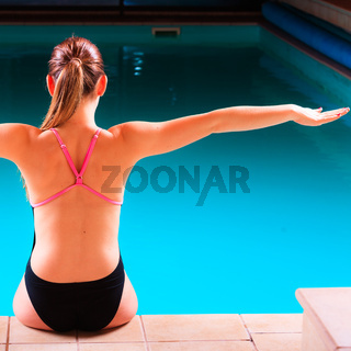 Girl swimmer muscular body  in swimsuit at poolside