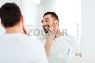 happy young man applying cream to face at bathroom