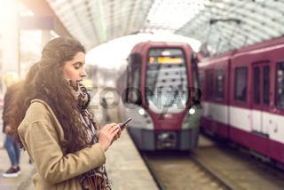 Woman at station with approaching train