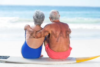 Cute mature couple sitting on a surfboard