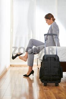 Geschäftsfrau mit Koffer sitzt auf Bett