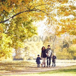 Family walking in autumn park