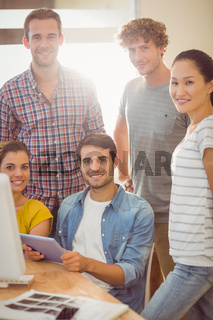 Creative business team gathered around a tablet