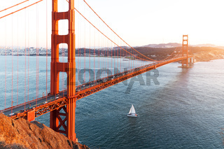 gold gate bridge and sailboat on sea in sunny day