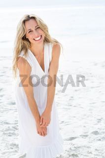 Smiling blonde in white dress looking at camera